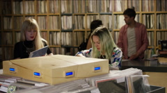 Friends selecting gramophone record in music store Stock Footage