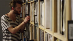 Young man looking through vinyl record collections at music shop Arkistovideo
