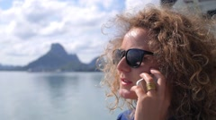 Young Woman Talking on Mobile Phone by the Sea - stock footage