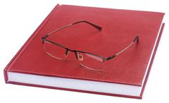 Maroon colored thesis paper with spectacles - stock photo