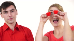 Couple. Serious man and crazy woman holds red hearts over eyes 4K Stock Footage