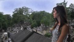 Young Woman Overlooks Graveyard from Hill Stock Footage