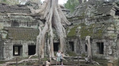 Tourists making photograph at overgrown temple in Ta Prohm,Siem Reap,Cambodia - stock footage