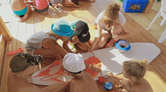 Children drawing on a Large Sheet Like Surf, compete - stock footage