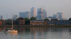 Small yacht passes Canary Wharf at sunrise Stock Footage