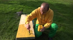 Painter man guy apply yellow color paint on wooden plank board with brush. 4K - stock footage