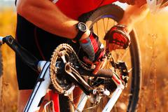 Cyclist repairs bicycle on the meadow Stock Photos