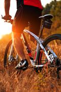 Cyclist on the Meadow Trail at tne Evening - stock photo