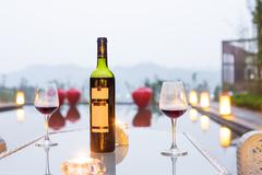 Red wine and glass on table outdoors in gloomy sky Stock Photos