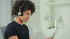 The young Afro-American listens to music in earphones - stock footage