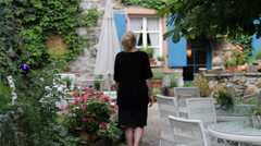 Woman Enters Cottage from Garden Stock Footage
