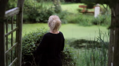 Woman Under Trellis Views Garden Pond Stock Footage