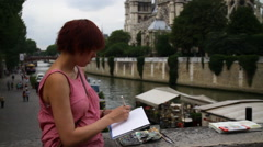 Female Artist Sketches Near Notre Dame Stock Footage
