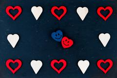 Vintage chalkboard with heart shapes and pair of smiling in love emoticons Stock Photos