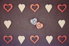 Vintage chalkboard with heart shapes and pair of smiling in love emoticons, v Stock Photos