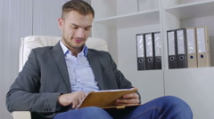 The young businessman reads news in the tablet Stock Footage