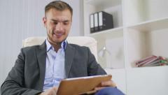 Portrait of the young businessman who communicates with friends on the tablet - stock footage