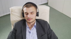 Young businessman relax with music sitting on a white arm chair Stock Footage