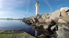 Lighthouse, calm sea and port in the background Stock Footage