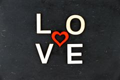 Word LOVE created of wood letters, red wooden heart shape in the middle, isol Stock Photos