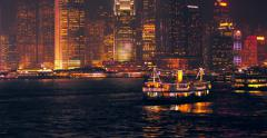 Tourist boat in Victoria harbor and lights of night city in Hong Kong downtown - stock footage
