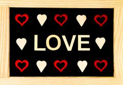 Wooden frame vintage chalkboard with Word LOVE created of wood letters and he Stock Photos