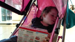 Little girl sleep in baby carriage. - stock footage