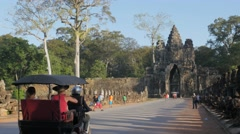 Tourists in Tuk Tuk over bridge to Angkor Thom,Siem Reap,Cambodia - stock footage