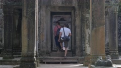Tourists walking through gates at Ta Prohm temple,Siem Reap,Cambodia - stock footage