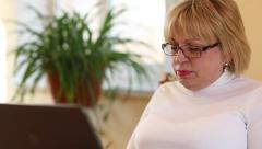 Senior woman types text using laptop. Woman with notebook - stock footage