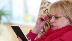 Senior woman sits on a sofa and reads electronic book. Woman reads a book Stock Footage