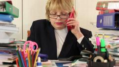 Senior woman bookkeeper sit at the table and communicates via smartphone - stock footage