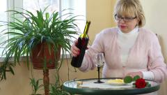 Woman sits at a table pours and drinks red wine Stock Footage