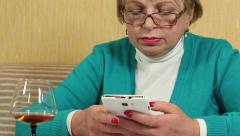 Woman with white smartphone writes sms and drinks brandy Stock Footage