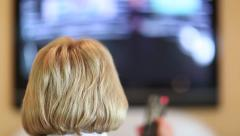 Woman with remote control switch tv channels Stock Footage