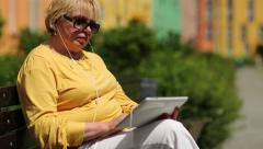 Woman in yellow jacket uses tablet computer.Woman holds Tablet-PC with earphones Stock Footage