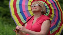 Blonde woman in glasses with colorful umbrella looks into the distance Stock Footage