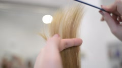Hairdresser stylist combing blonde hair tips - stock footage