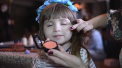 Make-up artist does the skin tone of a little girl model - stock footage