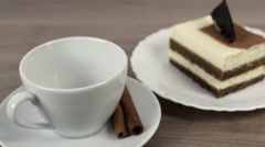 Coffee poured into a white cup on a wooden table with cake and cinnamon Stock Footage