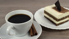 Putting sugar cube into a cup of coffee on a wooden table with tasty cake Stock Footage