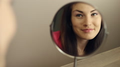 Beautiful young girl looking In The Mirror Stock Footage