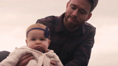 A young father holding up his sitting baby, outside on a fall day Stock Footage