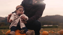 A baby sitting on a pumpkin at a pumpkin patch, with her dad holding her up Stock Footage