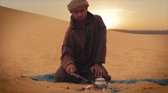 Man prepares tea in the desert Stock Footage