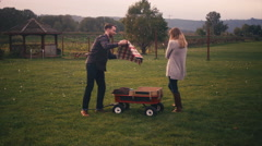 A young father lays out a blanket for a picnic while his wife holds their baby Stock Footage