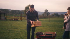 Man sets up a picnic basket and his wife hands him their baby and sits down Stock Footage