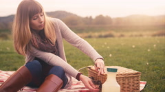 A young woman opening up a picnic basket while on a picnic with her family Stock Footage