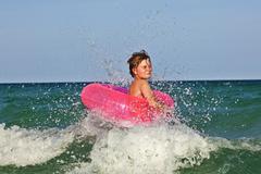 Boy in a swim ring has fun in the ocea Stock Photos