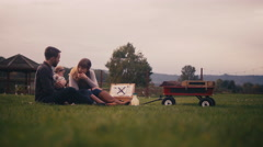 Family at a picnic on a fall day, and the baby accidentally hits her father Stock Footage